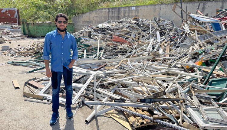 Fabio Piccione in mezzo a rifiuti di infissi e altri materiali